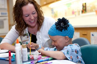 Child Life Specialist Rachel Niensteadt shares a laugh with one of the young patients at University of Iowa Children's Hospital.