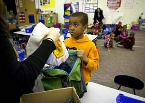 Samuel Jedo, an Edmunds Elementary first-grader in Des Moines, picks up food to take home after school. / Rodney White/The Register