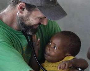Dr. Chris Buresh cuddles a a Haitian youngster, Wendly Steven, 13 months old, who has severe scar tissue on his hand from grabbing a piece of firewood/