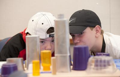 Summer camp students eye the model of the city they created.