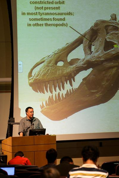 Professor Brochu behind podium with image of T. rex behind him on screen