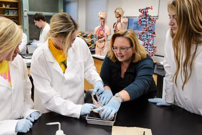 Instructor Kris Wiliams works with students dissecting a fetal pig