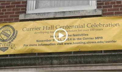 A Currier Hall Centennial Sign hangs beneath a window at UI's residence hall.
