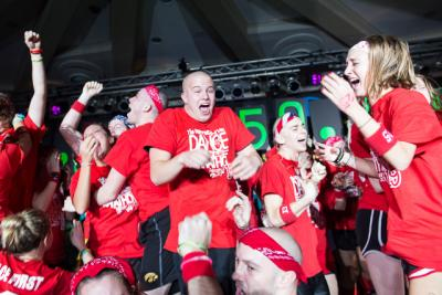 Students in red t-shirts dance and celebrate on a stage