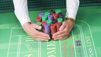 Dealer holding chips on gambling table.
