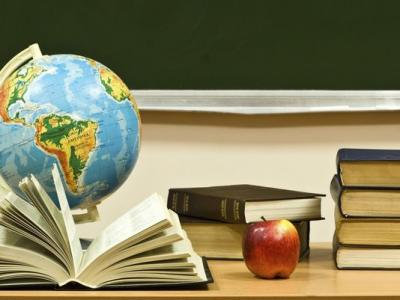 desk with books, apple, globe
