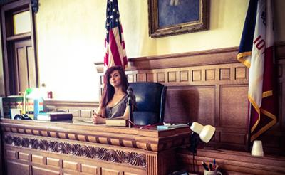 UI student Amanda Bartlett sits on the judge's seat in the district court while studying abroad