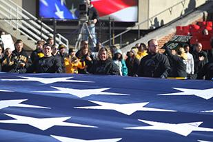 UI distance education student veteran helps carry U.S. flag at Kinnick during pregame activities.