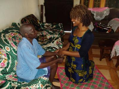 UI nursing and international studies student Jeannette George helps a young boy in Uganda and holds his hand