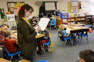 UI students stands in elementary school classroom