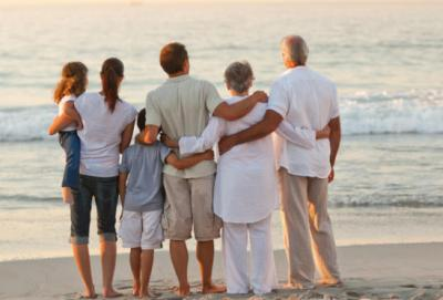A photo of an intergenerational family standing on a beach looking out at the waves with their arms around each other.