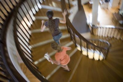 Two girls running up a spiral staircase at a museum