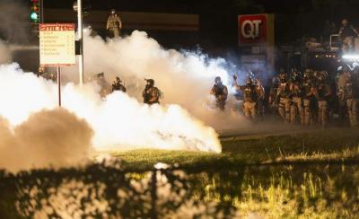 Riot police clear a street with smoke bombs while clashing with demonstrators in Ferguson, Missouri August 13, 2014. (REUTERS/Mario Anzuoni) Read more at http://thegazette.com/subject/news/iowa-professor-sheds-light-on-racial-tension-in-ferguson-20140821#