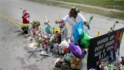 Beverly Scott of Chicago adds to the makeshift memorial in Ferguson, Missouri, for Michael Brown. Joe Raedle / Getty Images