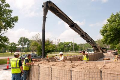 Workers fill temporary walls with sand at Mayflower.