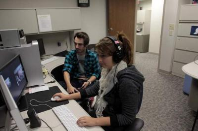 Meghan Horihan and Zach Phelps edit video Monday. The University of Iowa is partnering with Mediacom to broadcast content statewide from campus through the Hawkeye Network. / David Scrivner / Iowa City Press-Citizen