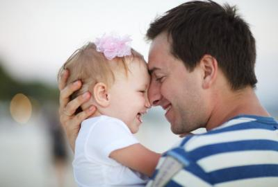 Photo of a Dad with his faced pressed against infant daughter while hugging her