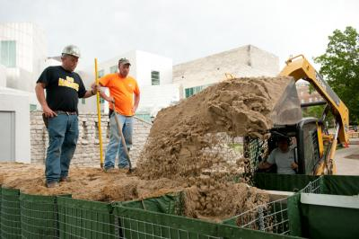 Workers, seen here late last week filling HESCO flood barriers with sand near the Iowa Advanced Technology Laboratories, got a well-deserved break Sunday after installing some seven miles of barrier around campus. Work will resume Monday morning. Photo by