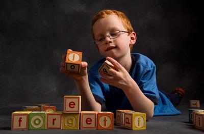 A boy makes words out of letter blocks