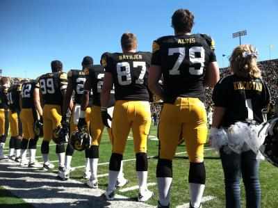 2012 Kid Captain Brandi Yates stands with the Iowa Hawkeyes during a home football game in 2012.