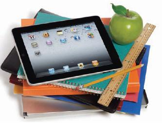 iPad on a stack of notebooks with apple and ruler