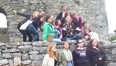 A group of UI students in the Irish Writing Program climb on stone structure in Ireland