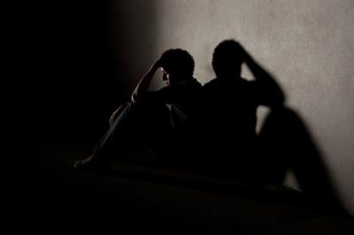 young man sitting in shadowy room