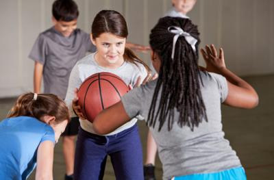 elementary aged children in gym class playing basketball