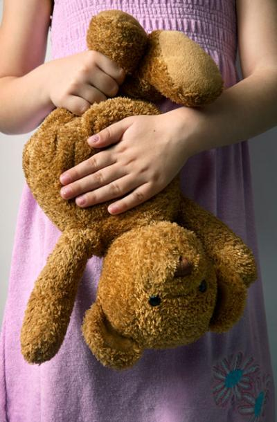 child clutching an upside down teddy bear