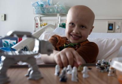 Seven-year-old Jacon Flesher of Manchester who spent his cancer remission collecting toys for other young oncology patients, plays a game while in bed