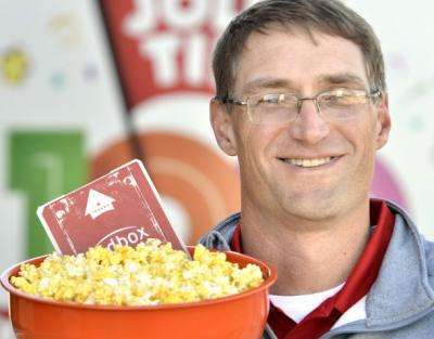 Steve Huisenga, vice-president of sales for Jolly Time Pop Corn, poses with a bowl of Jolly Time Blast O' Butter microwave popcorn and a Redbox movie on Oct. 29 outside Jolly Time's Sioux City offices. The Tippie College of business alum is now an executi