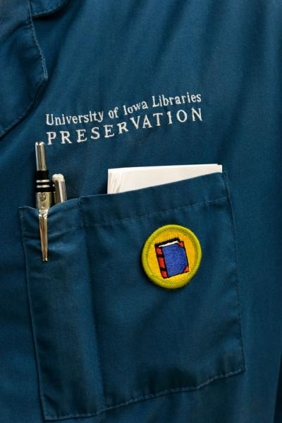 "the words ""University of Iowa Libraries Preservation"" are embroidered above the pocket of a blue lab coat"