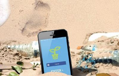 an iPhone is stuck in sand near a footprint.