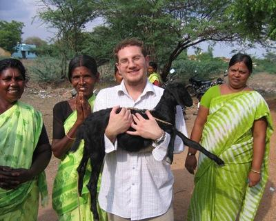 UI PhD student in geography Luke Juran, poses with several women while holding a goat during a Fulbright funded trip to India