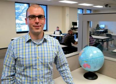 Matt Gilcrest poses by a globe in a TILE classroom