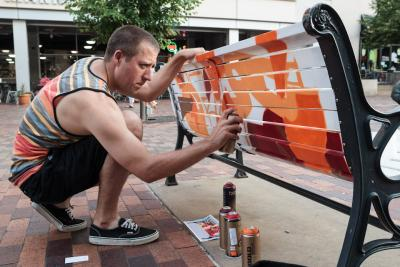 Man spray painting a bench