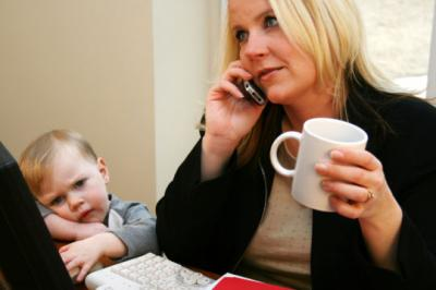 A mother talks on her cell phone, ignoring her young son.