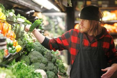 grocery worker stocking vegetables
