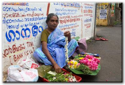 An image of a woman sitting on a street in India, surrounded by colorful flowers