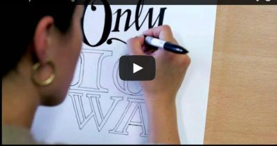 A person draws Only At Iowa as part of UI College of Education's Annual Report
