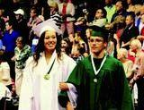 Pella student Lucas Rietveld in his high school graduation cap and gown with a female student also in cap and gown.