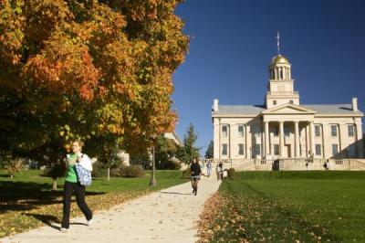 A UI student strolls on the Pentacrest in Autumn
