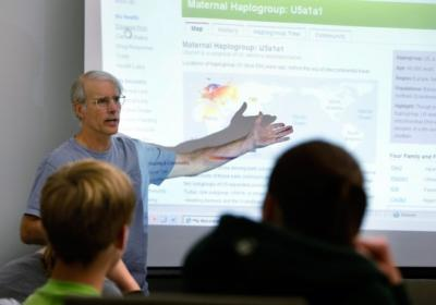 University of Iowa professor Jeff Murray gestures to a PowerPoint presentation while he talks about his genetic profile during an honors seminar on personal genetics.