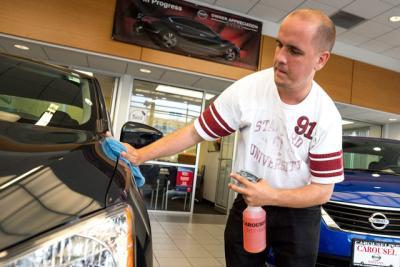 Daniel Peters cleans a car