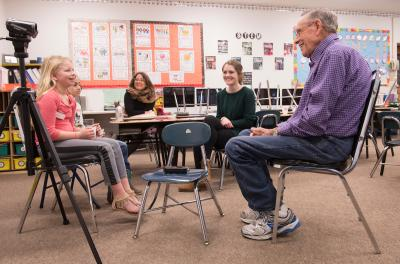 elementary students interview an older gentleman