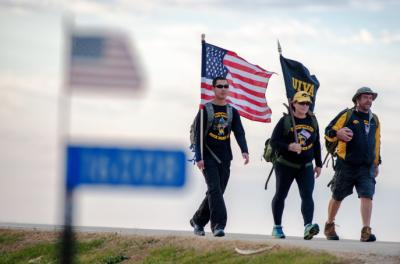 University of Iowa graduate and veteran Randy Miller (right), rucks alongside USAF veteran Patty Considine, and Iowa National Guardsman Jimmy Luu on Tuesday, Nov. 10 as part of the UIVA's Game Ball Ruck for veteran suicide awareness.