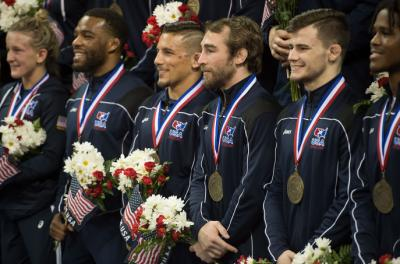 Daniel Dennis is surrounded by his Olympic teammates during the official team photo following the competition on Sunday.