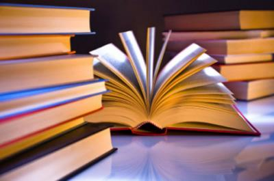 Photo illustration of a stack of books with one being open with the pages fanned