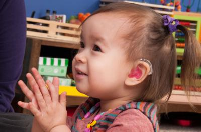 chid with hearing device