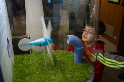 student looking at wind energy exhibit in mobile museum